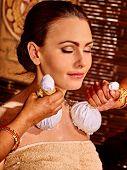 foto of panchakarma  - Woman having ayurvedic massage with pouch of rice - JPG