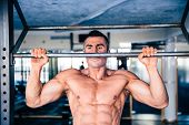 picture of pull up  - Muscular handsome man pulling up at gym - JPG