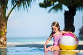 foto of girl toy  - Smiling toddler girl playing with toy in outdoor swimming pool - JPG