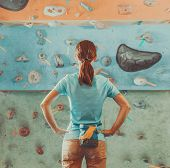 pic of climbing wall  - Young woman standing in front of a practical climbing wall indoor and preparing to climb - JPG