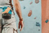 foto of climbing wall  - Young man standing in front of a practical climbing wall indoor and preparing to climb close - JPG