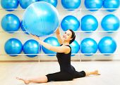 picture of do splits  - woman doing split with fitness ball during pilates stretching exercises in sport club - JPG