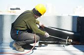 stock photo of membrane  - Roofer preparing part of bitumen roofing felt roll for melting by gas heater torch flame - JPG