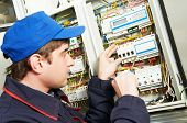 stock photo of fuse-box  - electrician builder engineer screwing equipment in fuse box - JPG