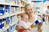 foto of little young child children girl toddler  - woman choosing children food with little baby child girl on hands during supermarket shopping - JPG
