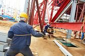 image of millwright  - builder worker at construction site installing metal construction frames - JPG