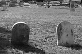 foto of funeral home  - set of two very old tombstones in a graveyard in black and white - JPG