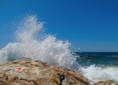 picture of starfish  - Powerful waves splashing on a rocky beach against clear blue sky and red starfish on a wet stone - JPG