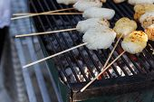 pic of brazier  - sticky rice with skewer are roasting on charcoal brazier - JPG