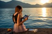 foto of sea-scape  - Young woman reading book and looking at beautiful sunrise on the pier with sea and mountains on background - JPG