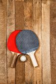 stock photo of ping pong  - Ping pong paddles with ball on vintage wooden background - JPG