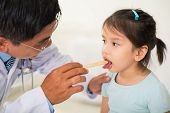 stock photo of tongue  - Doctor using tongue depressor to check throat of a girl  - JPG