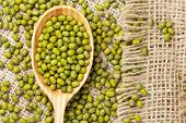picture of mung beans  - Heap of organic raw green mung bean lentils in wooden spoon on vintage textile background - JPG