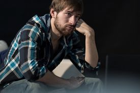stock photo of unemployed people  - Young unemployed man sitting on the sofa - JPG