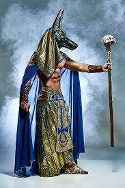 stock photo of pharaohs  - The man in the image of the ancient Egyptian Pharaoh  with a  mask of  Anubis on his face on blue background - JPG