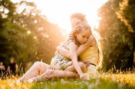 picture of cuddle  - Mother is cuddling her worried child outdoor in nature - JPG