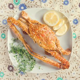 image of cooked blue crab  - Top view cooked delicious hot and spicy sauce blue crab on white plate with vintage tone - JPG