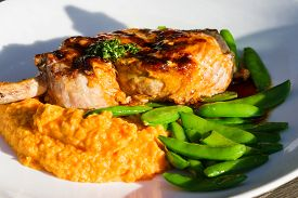 pic of sweet pea  - french cut pork chop served with a sweet potato puree and green peas on a white plate - JPG