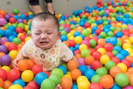 pic of cry  - A cute crying girl sitting in a colorful ball pit at a playground - JPG