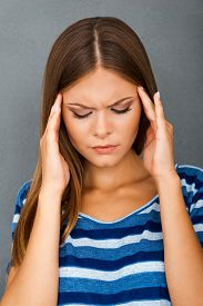 image of forehead  - Depressed young woman holding hands on her forehead while standing against grey background - JPG