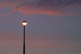 image of lamp post  - a lone lit street light with a sunset background - JPG