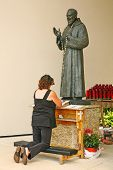 A woman worshiping  in front of Statue of Saint Padre Pio-