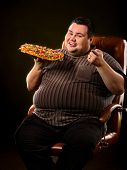 Fat man eating fast food and offers great pizza to customers. Male treats chic junk meal to friends. poster