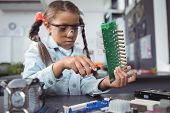 Concentrated elementary girl assembling circuit board on desk at electronics lab poster