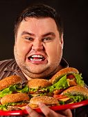 Fat man eating fast food hamberger and carries treat for friends on tray. Breakfast for overweight p poster