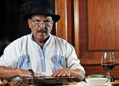 stock photo of tobaco leaf  - older senior man making luxury handmade cuban cigar - JPG