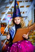 Beautiful little girl in a costume of witch celebrating halloween. Trick or treat. Halloween party. poster