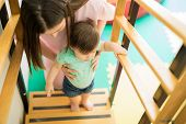 Woman Helping Baby Go Upstairs poster