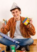 Repair home man holding paint roller for wallpaper. Male in newspaper cap renovation apartment. Stud poster