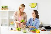 healthy eating, family and people concept - happy mother and daughter cooking vegetable salad for di poster