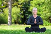 Mature middle aged fit healthy woman practicing yoga outside in a natural tranquil green environment poster