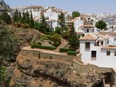 Image of white spanish buildings built on the cliffs edge at ronda spain.