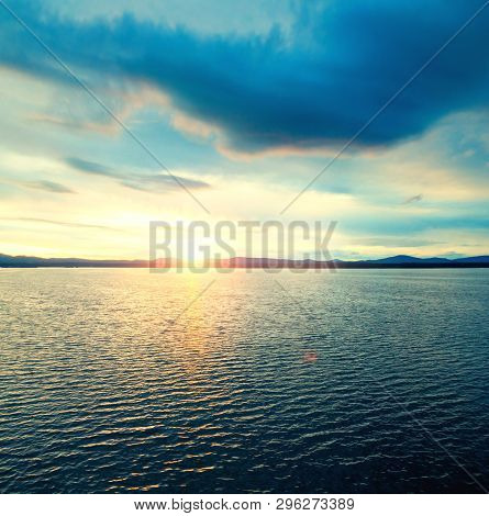 poster of Sea sunset landscape. Sea water surface lit by sunset light. Summer sunny sea water scene in vintage picturesque tones. Sea summer nature with mountains at the horizon - panoramic sea view