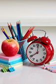 School supplies. Alarm clock with apple and school supplies. Back to school conceptual image. poster