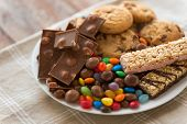 food, junk-food and unhealthy eating concept - close up of chocolate, oatmeal cookies, drop candies  poster