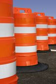 stock photo of road construction  - Orange road construction barrels with sharp focus on the second one - JPG