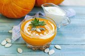 Roasted Pumpkin And Carrot Soup With Cream And Pumpkin Seeds On Blue Wooden Background. Vegetarian A poster