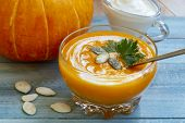 Home Made Pumpkin Cream Soup With Pumpkins And Parsley Leaves On Blue Wooden Table. Cream Soup Of Pu poster