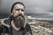 Guy Or Bearded Man At Cold Weather. Hipster With Thoughtful Face At Mountains. Man With Long Beard A poster