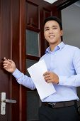 Young Asian Man With Resume Standing In Entrance Of Employer Office And Knocking On Wooden Door poster