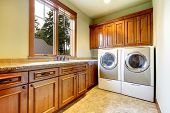 image of laundry  - Luxury laundry room with wood cabinets and tile floor - JPG