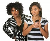stock photo of sneak  - Teenager sneaking cell phone as suspicious mother looks - JPG