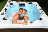 stock photo of bath tub  - Happy couple relaxing in hot tub - JPG