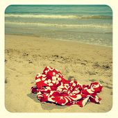 image of nudism  - picture of a red swimsuit laying on the sand of a beach - JPG