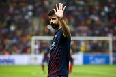 KUALA LUMPUR - AUGUST 10: FC Barcelona's player Gerard Pique waves to fans warm-up before the match