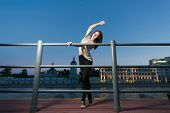 A young woman is standing in a ballet position using as a barre the railing on the waterfront